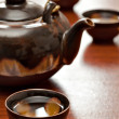 Cup of tea and teapot, wooden desk — Stock Photo