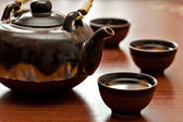 Xícara de chá e bule de chá, mesa de madeira — Foto Stock