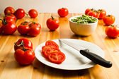 Sliced Vine Tomato, Rocket And Knife On A Kitchen Table — Stock Photo