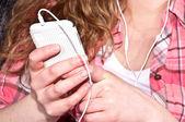 Mit hilfe eines mobiltelefons während des listeng musik — Stockfoto