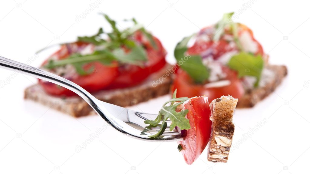 Vegetarian and healthy piece of tomato bread on a fork isolated on white background — Stock Photo #10466372