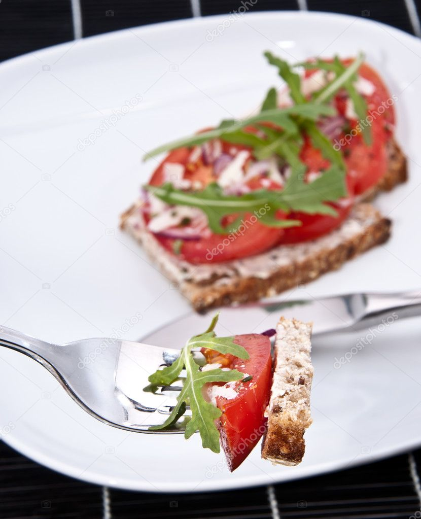 Vegetarian and healthy piece of tomato bread on a fork on a black tablecloth — Stock Photo #10466379