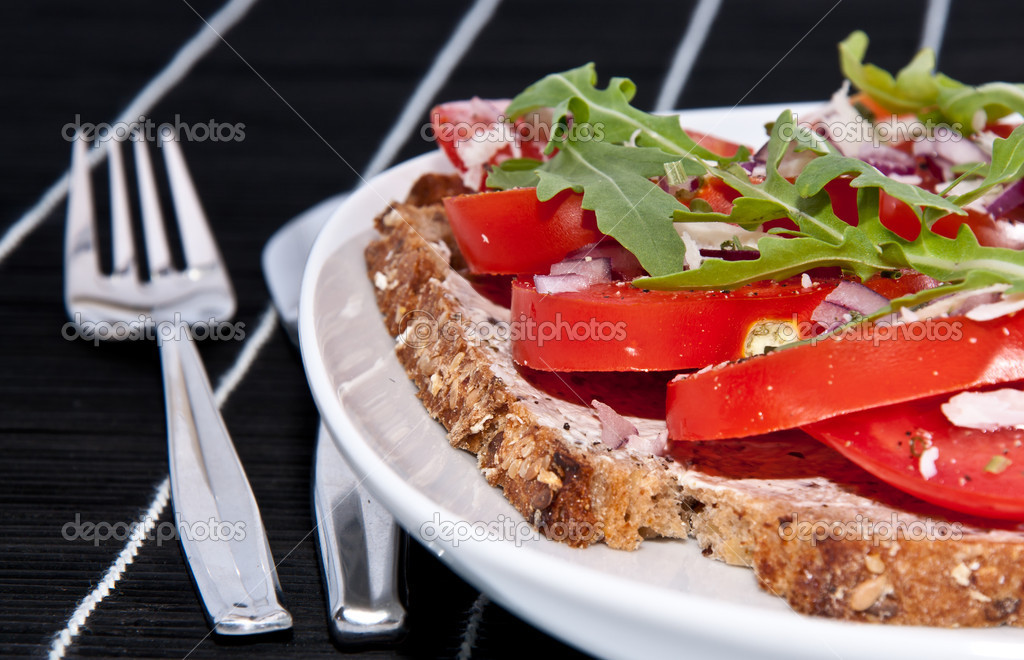 Fresh made tomato bread with onion, cream cheese, rocket salad and Parmesan cheese on a black tablecloth with cutlery — Stock Photo #10466393
