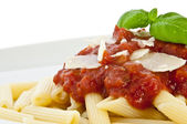 Penne with sauce, basil and chese on a plate (macro view) — Stock Photo