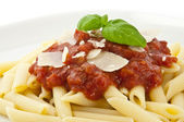 Macro view of penne, sauce and cheese decorated with fresh basil — Stock Photo