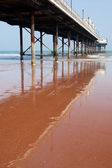 Pier reflected in the red sand that is typical of the South Devon Coast, Paignton England. — Stock Photo