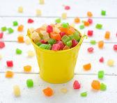 Coloridas frutas confitadas en un pequeño cubo — Foto de Stock