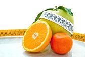 Orange, apples & mandarine measured by tape meter — Stock Photo