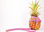 Pineapple with measuring tape isolated on white — Stock Photo