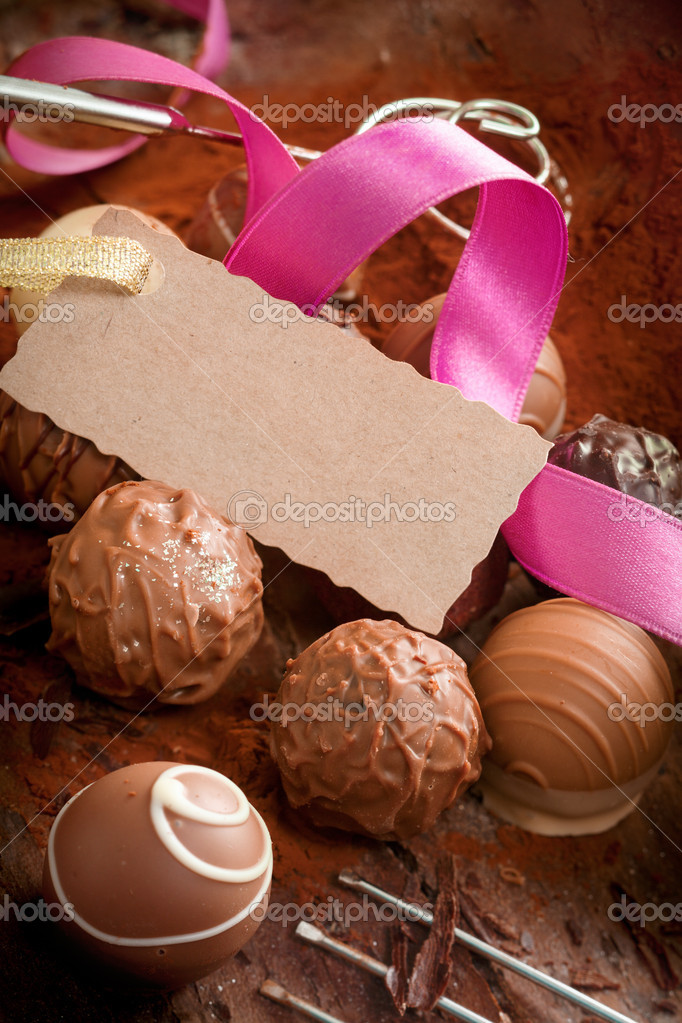 Handmade gourmet chocolates with a decorative pink ribbon and a luxury testured blank gift tag with a serrated edge — Stock Photo #9684001