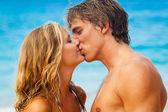 Jong koppel zoenen op tropisch strand — Stockfoto