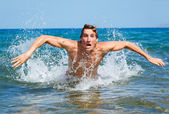 Man swimming butterfly strokes in ocean — Stock Photo
