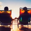 Senior couple of old man and woman sitting on the beach watching — Stock Photo