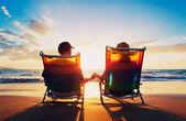 Senior pareja de hombre y mujer sentada en la playa mirando — Foto de Stock