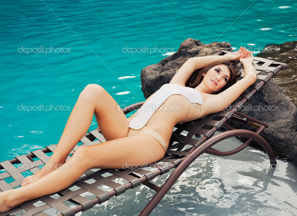 Beautiful Girl Relaxing by the Pool at Tropical Resort  Stock Photo #10561494