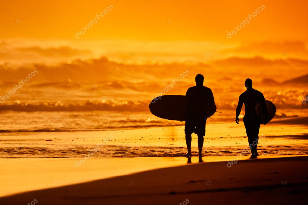 Silhouettes of Surfers on the Beach at Sunset — Stock Photo #8817674