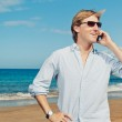 Business man calling by cell phone on the beach — Stock Photo