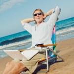 attraktiv ung avkopplande på stranden med bärbar dator — Stockfoto