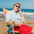 Business man calling by cell phone at the beach — Stock Photo