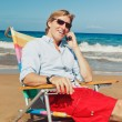 Business man calling by cell phone at the beach — Stock Photo #9758135