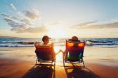 Glad romantiska par njuter av vacker solnedgång på stranden — Stock fotografie