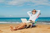 Genç çekici adam dizüstü bilgisayar ile sahilde rahatlatıcı — Stok fotoğraf