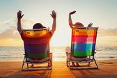 Glad romantiska par njuter av vacker solnedgång på stranden — Stockfoto