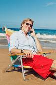 Homme d'affaires appeler par téléphone cellulaire à la plage — Photo