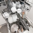 Dish washer with clean and shiny dishes and kitchenware - Stock Photo