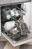 Dish washer with dirty dishes and kitchenware — Stock Photo