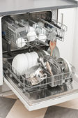 Dish washer with clean and shiny dishes and kitchenware — Stock Photo