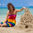 A woman building a sandcastle - Stock Photo