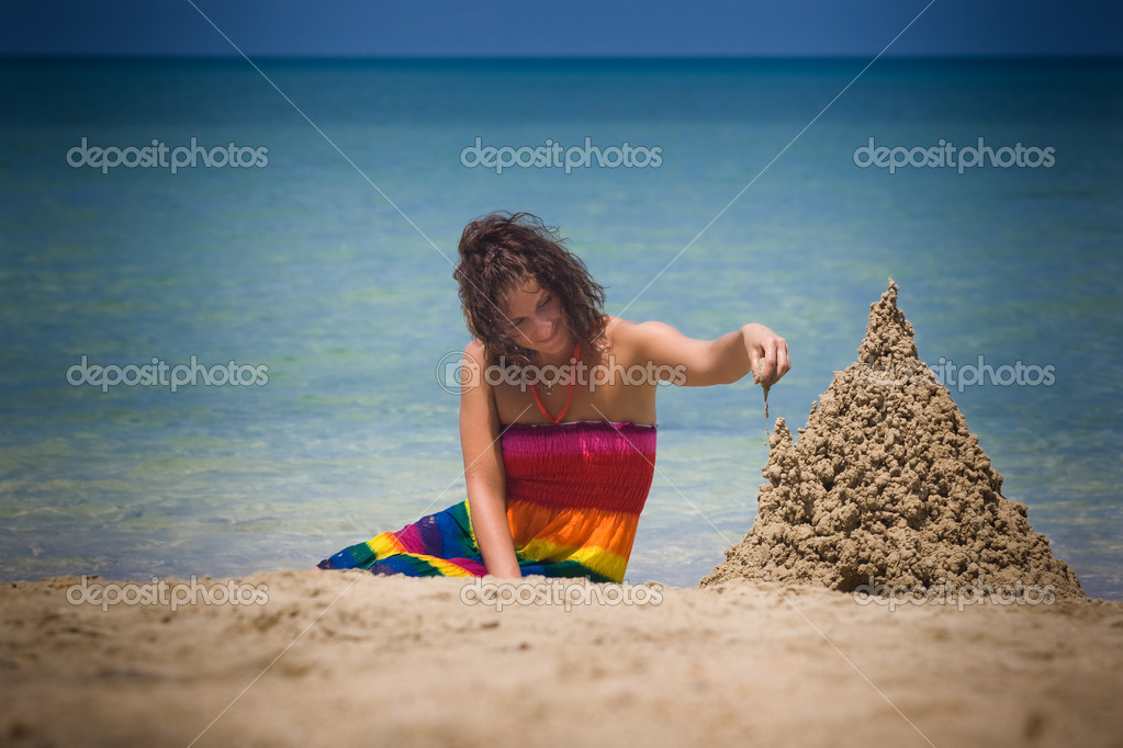A woman building a sandcastle on the beach. — Stock Photo #8532410