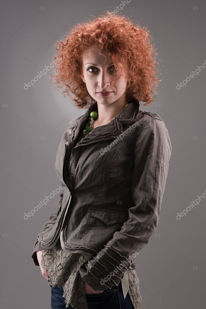 Beautiful model with curly red hair on gray background. — Stock Photo #8563535
