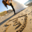 Happy couple and sand of love — Stockfoto