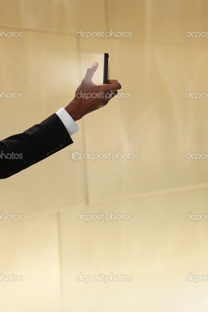 Concept photo of a man holding a glowing cell phone against neutral warm background with lots of copy space — Stock Photo #10111416