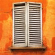 Shutters on orange wall — Stock Photo