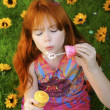 Red headed girl blowing bubbles - Stock Photo