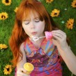 Stock Photo: Red headed girl blowing bubbles