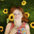 Stock Photo: Little girl with sunflowers