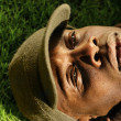 Close-up of African-American man laying on grass - Stock Photo