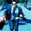 Young man running with briefcase - Stock Photo