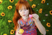 Red headed girl blowing bubbles — Stock Photo