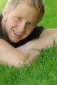 Young male smiling on grass — Stock Photo