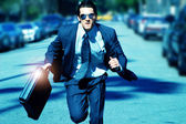 Young man running with briefcase — Stock Photo
