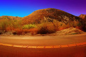 Red hill with curved road — Stock Photo
