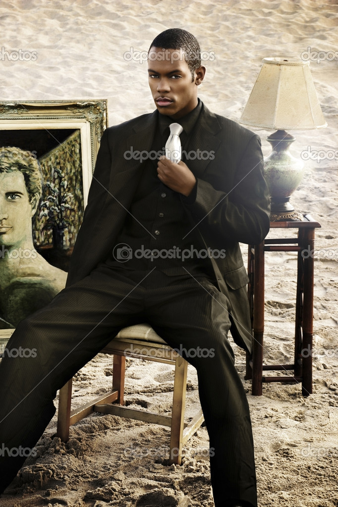Young man sitting on chair with furniture on the beach  Stock Photo #8449136