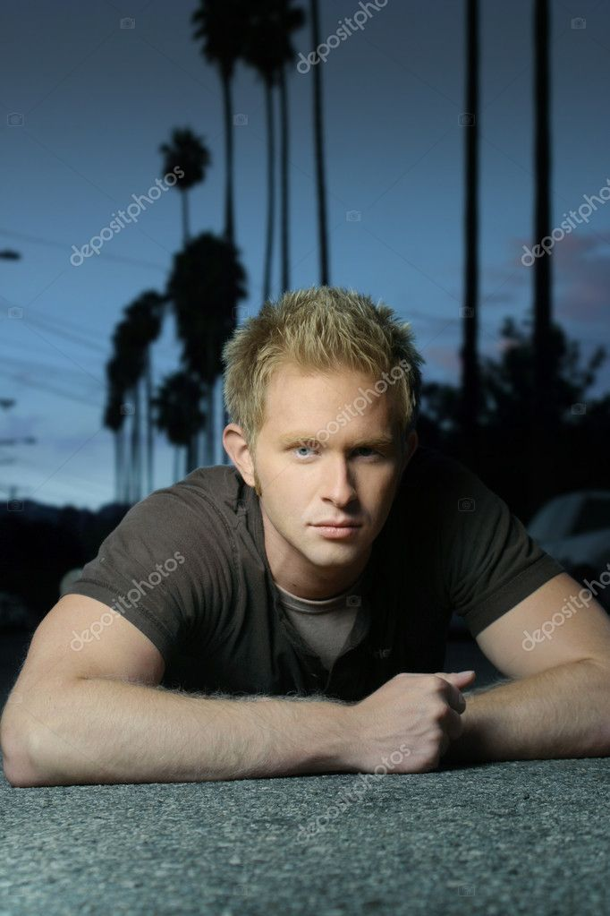 Blond young man laying down on street with sky behind  Stock Photo #8449391