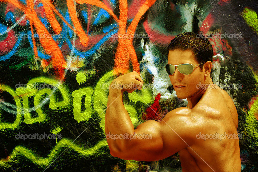 Bodybuilder flexing bicep against graffiti — Stock Photo #8451783