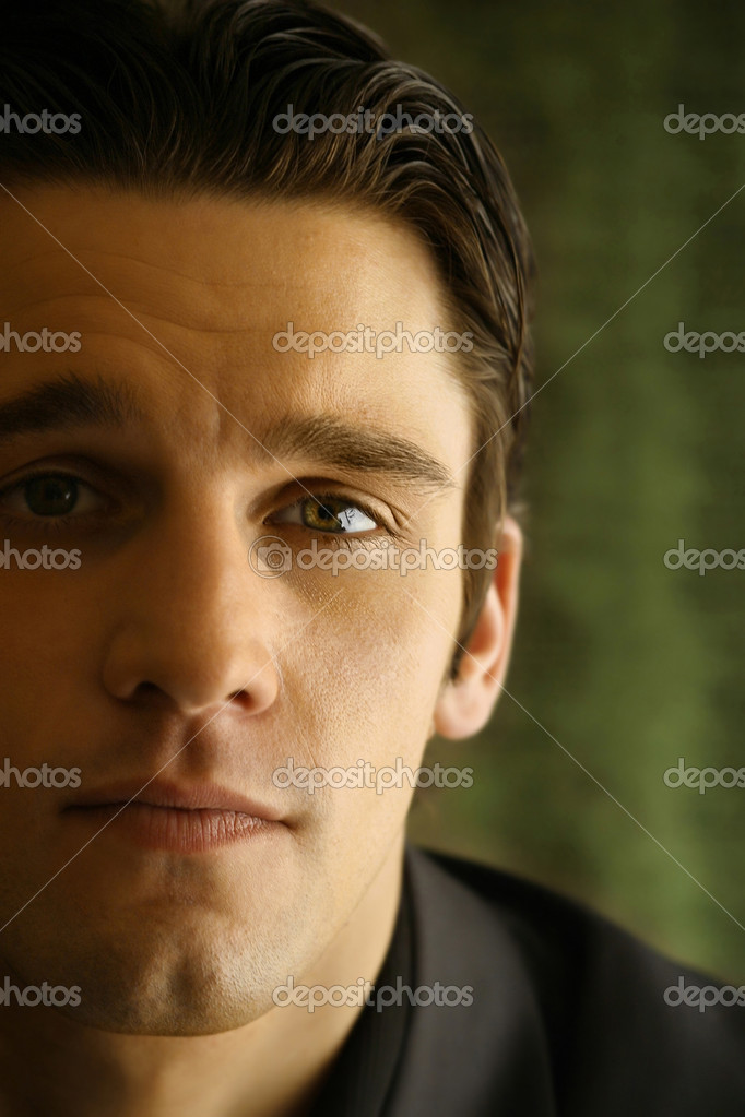 Close up of a young man's face against green background  Stock Photo #8453047